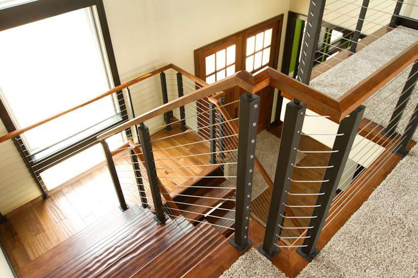 Custom cable railing system with metal posts and wood handrails