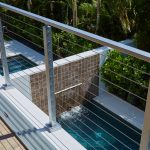 cable railing surface mount posts overlooking a beautiful pool in a Florida condo