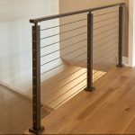 Balcony rod railing with black surface mount posts and handrail